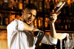 Der brandstiftende Barmixer gießt schön Alkohol vom bott Lizenzfreies Stockbild