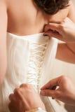 Der Braut helfen, ihr Hochzeitskleid an zu setzen stockbild