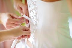 Der Braut helfen, ihr Hochzeitskleid an zu setzen lizenzfreie stockfotografie