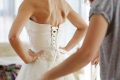 Der Braut helfen, ihr Kleid ein zu setzen stockfotos