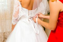 Der Braut helfen, im Hochzeitskleid anzukleiden Stockfotos