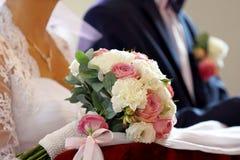 Der Brautblumenstrauß an der Kirche auf dem Kneeler Lizenzfreies Stockfoto