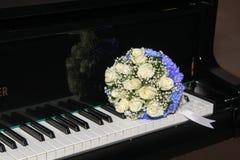 Der Brautblumenstrauß von den Rosen liegt auf Klavierschlüsseln Lizenzfreie Stockfotos