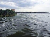Der breite Fluss an einem grauen bewölkten Tag Gemütliche Brücke für die Fischerei Silberne Wellen auf dunklem Wasser stockfoto