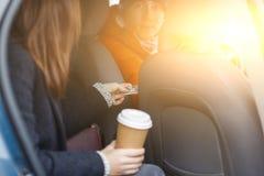 Der Brunette, der im Taxi sitzt, sendet Bargeld für Durchgangsfahrer Stockbilder
