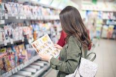 Der Brunette steht im Mall nahe den Zeitschriftenregalen und betrachtet den Produktkatalog lizenzfreie stockfotos