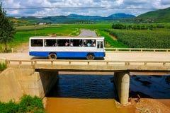 Der Bus, der auf die Brücke in einer unbekannten Landschaft von Nordkorea, DPRK fährt Stockbilder