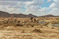 Der Bus geht auf die Straße, die durch die felsige Sahara-Wüste, Tunesien überschreitet Lizenzfreie Stockfotografie