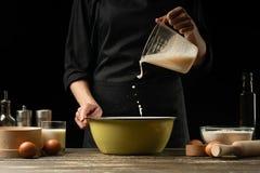 Der Chef bereitet den Teig für Brot, Pizza und Bonbons zu Das Konzept des Lebensmittels Auf einem schwarzen Hintergrund frierend  stockbild