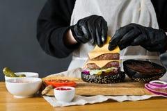 Der Chef bereitet einen enormen Burger zu Das Konzept des Kochens des schwarzen Cheeseburgers Selbst gemachtes Hamburgerrezept stockbilder