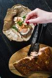 Der Chef besprüht Petersilie auf einem Sandwich mit Leiste des geräucherten Lachses auf Schwarzbrot und Weichkäse stockfoto