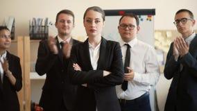 Der Chef, den Mädchen sicher mit ihren Waffen steht, kreuzte auf ihrem Kasten hinter ihr sind ihre internationalen Untergebenen stock video footage