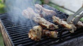 Der Chef, der saftiges und köstliches Rindfleisch dreht, haftet auf dem Grill stock video