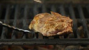 Der Chef dreht ein großes saftiges und starkes Stück Rindfleisch, Lamm oder Schweinefleisch auf dem Grill mit den Zangen und dann stock video footage