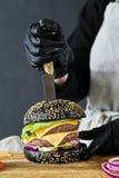Der Chef, der einen saftigen Burger kocht Das Konzept des Kochens des schwarzen Cheeseburgers Selbst gemachtes Hamburgerrezept lizenzfreie stockfotografie