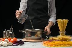 Der Chef gießt Wasser in die Wanne, auf einem schwarzen Hintergrund, mit Teigwaren auf dem Tisch, Gemüse und Spaghettis, Pilze Da lizenzfreie stockfotos