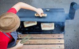 Der Chef im Hut backt ein Panini im Ofen auf den Kohlen stockfoto