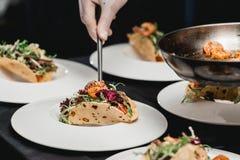 Der Chef im Restaurant, der würzige Garnelen-Tacos mit Kohlsalat und Salsa macht lizenzfreies stockfoto
