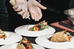 Der Chef im Restaurant, der würzige Garnelen-Tacos mit Kohlsalat und Salsa macht lizenzfreie stockfotos