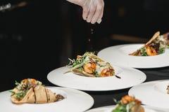 Der Chef im Restaurant, der würzige Garnelen-Tacos mit Kohlsalat und Salsa macht lizenzfreies stockbild