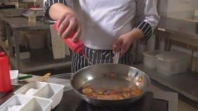 Der Chef kocht Gemüse und Fleisch in einer Wanne mit dem Feuer Restaurant stock footage