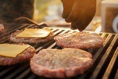 Der Chef salzt ein Kotelett auf dem Grill Straßenlebensmittel stockfoto