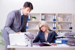 Der Chef, der seinem behilflichen Sekretär Mehrarbeit holt lizenzfreie stockfotografie