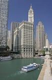 Der Chicago River, das Kreuzfahrtboot und die Wolkenkratzer einschließlich Wrigley-Gebäude Stockfotografie
