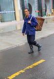 Der chinesische alte Mann, der einen Bambus auf der regnerischen Straße zurückbringt Lizenzfreies Stockbild
