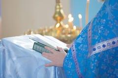 Der christliche Priester, der eine Bibel hält stockfotos