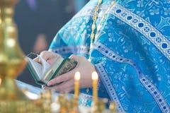 Der christliche Priester, der eine Bibel hält stockfotografie
