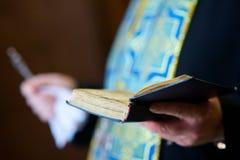 Der christliche Priester, der eine Bibel hält lizenzfreie stockfotografie