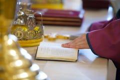 Der christliche Priester, der eine Bibel hält stockbilder