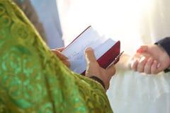 Der christliche Priester, der eine Bibel hält lizenzfreie stockfotos