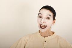 Der Clown steht vor einer Kamera und macht ein Gesicht Stockfotografie