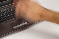 Der Computer möchte nicht richtig arbeiten Eine männliche Hand, die heftig eine Laptopberührungsfläche schlägt lizenzfreie stockbilder