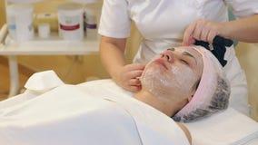 Der Cosmetologist, der Verfahren der Reinigung und des Befeuchtens der Haut tut stock video footage