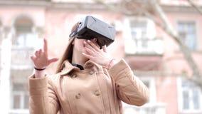 Der Cyberspacevirtuellen realität der jungen glücklichen Frau outwear tragende Kopfhörergläser vr in der Beige Mantel hat Spaß dr stock video