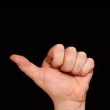 Der Daumen der linken Hand Männer ` s Hand, die einen Finger auf einem schwarzen Hintergrund zeigt Stockfotografie
