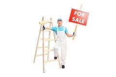 Der Dekorateur, der Farbenrolle halten und a für Verkauf unterzeichnen stockfoto