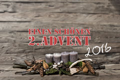 Der Dekorationseinführung 2016 der frohen Weihnachten brennende graue Kerze verwischte Hintergrundtextnachrichtdeutschen 2. Stockfoto