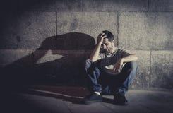 Der deprimierte junge Mann, der auf Straße sitzt, rieb mit Schatten auf Betonmauer Stockfotos