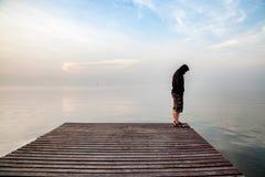 Der deprimierte junge Mann, der einen schwarzen Hoodie steht auf Holzbrücke trägt, verlängerte in das Meer, das unten schaut und  Stockbild