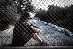 Der deprimierte Mann, der einen schwarzen Hoodie sitzt aus den Grund trägt, sind s Lizenzfreie Stockbilder