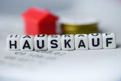 Der deutsche Wort HAUS-KAUF, der durch Alphabet gebildet wird, blockiert: HAUSKAUF Lizenzfreies Stockbild