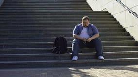 Der dicke Mann, der Musik auf Treppe, Einsamkeit hört, Übergewicht verursacht Unsicherheit stock video