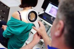 Der Doktor überprüft die Muttermale des Patienten durch eine Lupe Lizenzfreie Stockfotografie