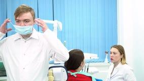 Der Doktor bereitet sich für das bevorstehende Verfahren vor und setzt sich auf Schutzmaske mit seinem Assistenten, der mit Pati stock video