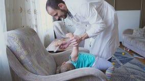 Der Doktor besucht den Babypatienten zu Hause Der Doktor bestimmt die geduldige ` s Kehle stock video footage
