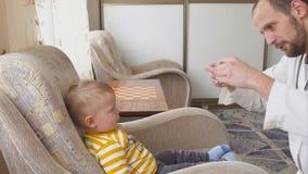 Der Doktor besucht den Babypatienten zu Hause Doktor gibt dem Baby Medizin von einem Löffel stock video
